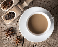 热的饮料的香料在一个杯子的分裂树桩与奶油的热的咖啡旁边 免版税库存图片