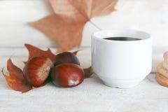 热的饮料,咖啡在一传统加泰罗尼亚语万圣夜党castanyada的 在叶子和白色木桌的三个栗子 库存图片