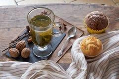 热的绿茶和新鲜的松饼在一张木桌上 免版税库存图片