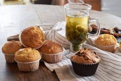热的绿茶和新鲜的松饼在一张木桌上 免版税库存照片