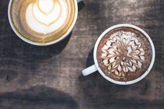 热的绿茶拿铁艺术和热巧克力在木 免版税库存图片