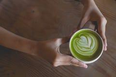 热的绿茶拿铁艺术在手边在桌咖啡馆商店 库存照片