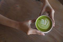 热的绿茶拿铁艺术在手边在桌咖啡馆商店 免版税图库摄影