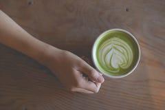 热的绿茶拿铁艺术在手边在桌咖啡馆商店 库存图片