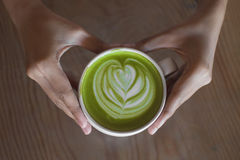 热的绿茶拿铁艺术在手边在桌咖啡馆商店 免版税库存图片