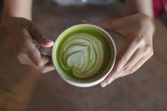 热的绿茶拿铁艺术在手边在桌咖啡馆商店 图库摄影
