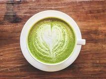 热的matcha绿茶牛奶拿铁顶视图用乳脂状的牛奶是心形的样式和一点糖在一个杯子在木 免版税库存图片