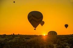 热空气剪影迅速增加飞行在谷在卡帕多细亚,安纳托利亚,土耳其 火山的山在Goreme 免版税库存照片