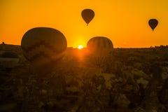 热空气剪影迅速增加飞行在谷在卡帕多细亚,安纳托利亚,土耳其 火山的山在Goreme 免版税图库摄影