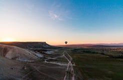 热空气在地面上的气球阴影在飞行在谷和山的日出期间 免版税库存照片