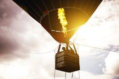 热空气在多云天空的气球飞行在日出-气球在天空的剪影飞行的图象 免版税库存图片