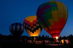 热空气气球在弯俄勒冈的晚上焕发 库存图片