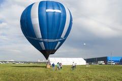 热空气气球在领域登陆了在黎明 免版税库存照片