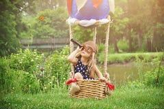 热空气气球的假装试验的女孩旅行 免版税库存照片
