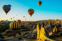 热空气气球离开在卡帕多细亚, Goreme,土耳其的日出 库存照片