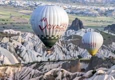 热空气气球通过美好的卡帕多细亚风景漂浮靠近Goreme镇在土耳其在日出 免版税图库摄影