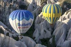 热空气气球通过美好的卡帕多细亚风景漂浮靠近Goreme镇在土耳其在日出 免版税库存照片