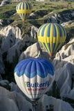 热空气气球通过美好的卡帕多细亚风景漂浮靠近Goreme镇在土耳其在日出 库存照片
