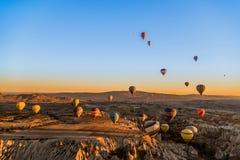 热空气气球鸟瞰图飞行在卡帕多细亚在日出期间,土耳其的 库存图片