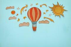 热空气气球,空间元素形状裁减从纸和绘在木蓝色背景 免版税库存照片
