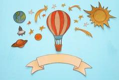 热空气气球,空间元素形状裁减从纸和绘在木蓝色背景 免版税图库摄影