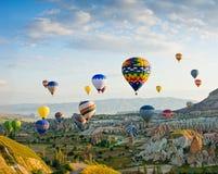 热空气迅速增加飞行在红色谷在卡帕多细亚,土耳其 库存照片