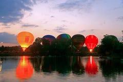 热空气飞行的baloons startung在晚上天空 免版税库存图片