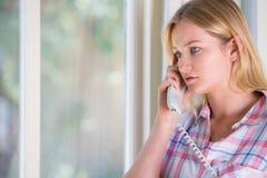 给热线服务电话打电话的急切少妇 免版税库存照片