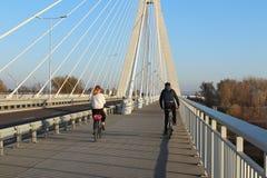 热舒夫,波兰- 9 9 2018年:有女孩乘坐的自行车的一个人在横跨Wislok河的停止路桥梁晴朗的,clea 库存图片