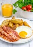 热诚的早餐用烟肉、煎蛋、土豆和橙汁 免版税图库摄影