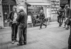 热那亚,意大利- 2016年4月21日:两个人遇见在老商业ital 免版税库存照片