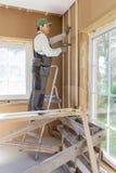 热量地绝缘eco木制框架房子的建筑工人 库存照片