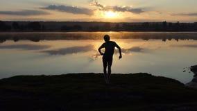 热闹的人在湖跳舞迪斯科样式在日落在slo mo 股票录像