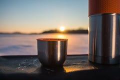 从热水瓶的杯在日落 免版税库存照片