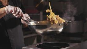 烹调一个面条用肉和菜的厨师特写镜头在铁锅平底锅 股票视频