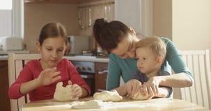 烹调一起揉的面团的家庭在有母亲女儿和儿子的厨房里在好日子 影视素材