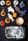 烹调万圣夜与棒,骨骼,在烤板附近的鬼魂甜点的姜饼曲奇饼 黑背景顶视图大模型 免版税库存照片