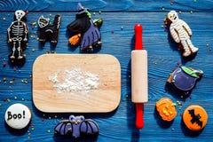 烹调万圣夜在骨骼,妈咪形状的姜饼曲奇饼  甜点临近书桌和滚针 蓝色背景上面 免版税库存照片