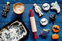 烹调万圣夜在骨骼,妈咪形状的姜饼曲奇饼  甜点临近书桌和滚针 蓝色背景上面 库存图片