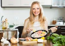 烹调三文鱼用柠檬的微笑的妇女 免版税库存图片