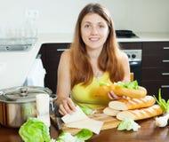 烹调三明治用乳酪的愉快的妇女 免版税库存照片