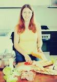 烹调三明治的愉快的妇女 免版税库存照片