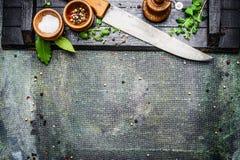 烹调与厨刀的集合有桌在土气背景,顶视图的香料、盐和胡椒磨的 库存图片