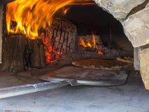 烹调与在一个室外乡下烤箱的木柴 免版税库存照片