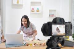 烹调与在手提电脑的收据的妇女在厨房里,当录音做录影 库存照片