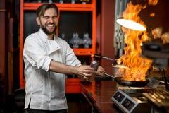 烹调与在煎锅的大火的疯狂的厨师 库存图片