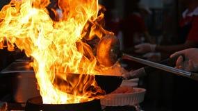 烹调与在煎锅的火的厨师 免版税库存图片