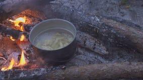 烹调与大锅的面团在营火在晚上森林厨师搅动与匙子的食物 特写镜头 股票视频