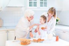 烹调与女儿和孙女的祖母 免版税库存图片