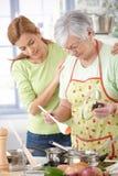 烹调与女儿的高级母亲 免版税库存图片